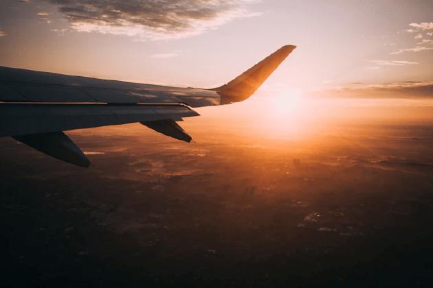 Passenger aircraft wing against setting sun