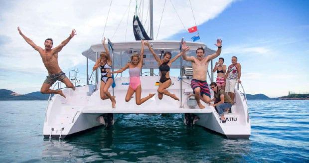 Catamaran at sea with people jumping