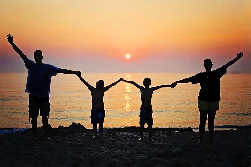 Family silhouette against ocean sunset